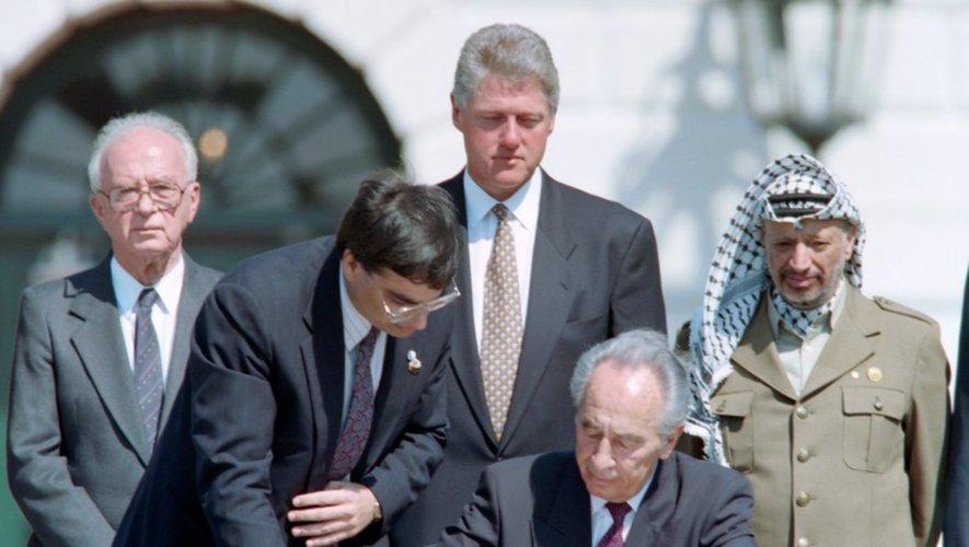 Le 13 septembre 1993, alors ministre des affaires étrangères d'Israël, Shimon Peres (assis) signe l'historique Accord d'Oslo à la maison Blanche sous le regard de gauche à droite du Premier ministre israélien Yitzhak Rabin, du président américain Bill Clinton et du leader palestinien Yasser Arafat