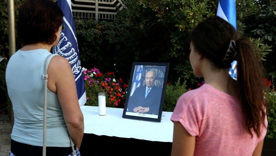 Des Israéliennes se recueillent devant le portrait de l'ancien président Shimon Peres devant la résidence présidentielle, le 28 septembre 2016 à Jérusalem