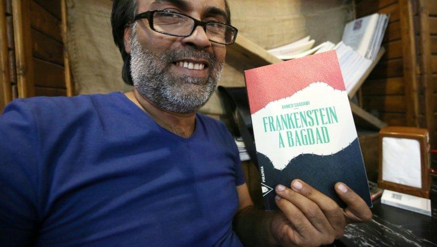 """L'écrivain irakien Ahmed Saadawi pose avec son roman """"Frankenstein a Bagdad"""" le 4 août 2016 à Bagdad"""