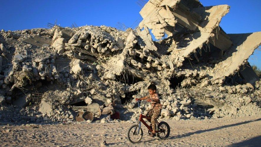 Un enfant syrien fait du vélo devant un immeuble détruit le 27 septembre 2016 à Daraa (Syrie)