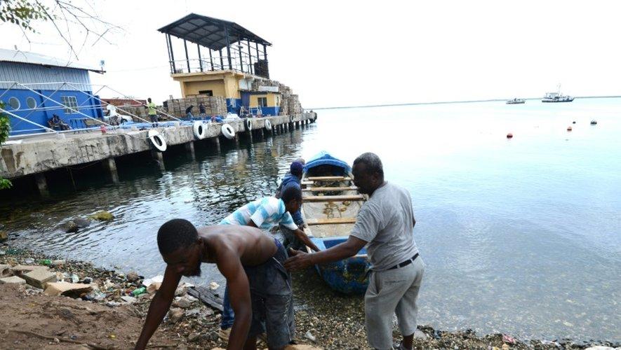 Des pêcheurs tirent un bateau pour le mettre à l'abri avant l'arrivée de l'ouragan Matthew à Kingston le 1er octobre 2016