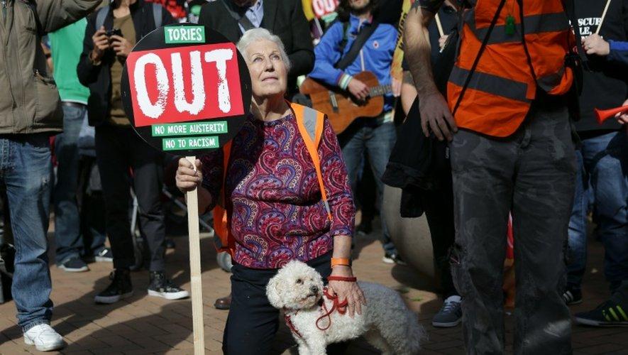 """Une pancarte disant """"Non à l'austérité"""", """"les Tories dehors"""" et """"Non au racisme"""" est brandie par une manifestante à Birmingham, peu avant l'ouverture du congrès annuel des conservateurs britanniques, le 2 octobre 2016"""