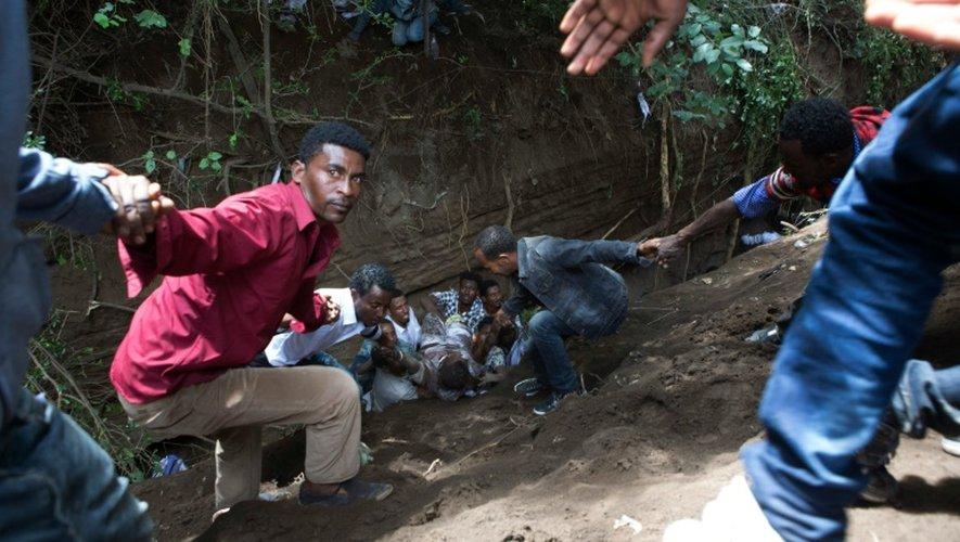 Des hommes extraient un blessé après des affrontements entre policiers et manifestants suivis d'une bousculade mortelle à Bishoftu (sud d'Addis Abeba) , le 2 octobre 2016