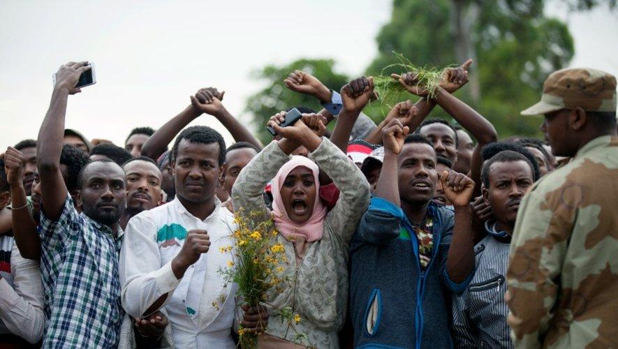 Des habitants de Bishoftu (sud d'Addis Abeba) brandissent leurs bras croisés au dessus de la tête, geste devenu symbole de la contestation des Oromo face aux autorités éthiopiennes, le 2 octobre 2016