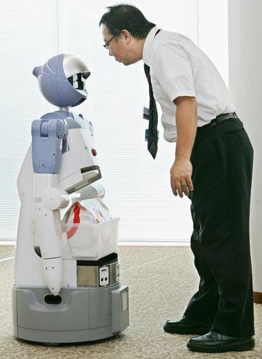 """Le robot de service à la personne """"Enon"""" développé par Fujitsu communique avec un ingénieur avant de transporter un paquet, à Tokyo le 13 septembre 2005"""