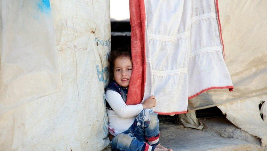 Une jeune  syrienne sort d'une tente dans un camp de réfugiés de la Békaa, dans l'est du Liban, le 15 juillet 2016