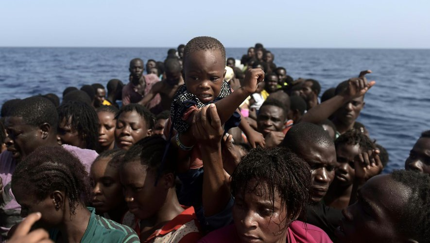 Un enfant est hissé par des migrants qui attendent à bord d'une embarcation de fortune d'être secourus par l'ONG espagnole ProActiva Open Arms, au large de la Libye, en mer Méditerranée, le 4 octobre 2016.