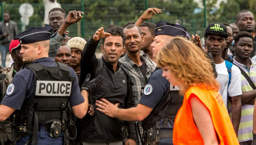 """Des habitants de la """"Jungle"""" de Calais interpellent une responsable de la préfecture chargée de sélectionner les migrants envoyés dans des Centres d'accueil et d'orientation (CAO), le 13 septembre 2016 à Calais"""