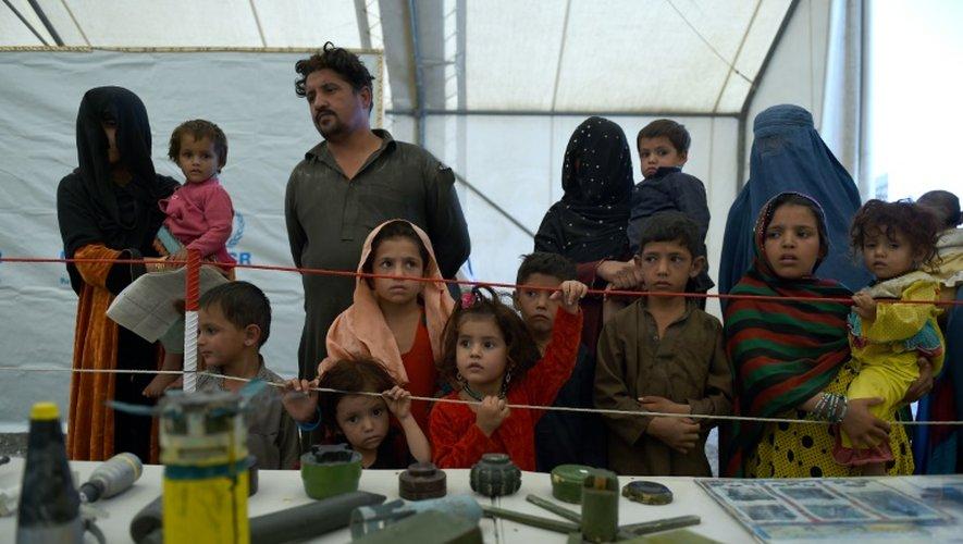 Des réfugiés afghans sont instruits des dangers des bombes et mines dispersés en Afghanistan dans un camp du HCR, près de Kaboul, le 27 septembre 2016