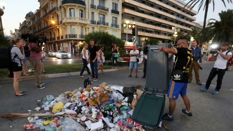 Un homme déverse des ordures à l'endroit où Mohamed Lahouaiej Bouhlel a été tué, sur la Promenade des Anglais, à Nice, le 18 juillet 2016