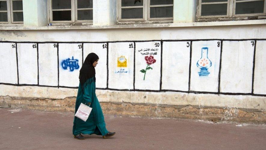 Une marocaine passe devant les symboles électoraux ds partis engagés dans les élections législatives au Maroc, le 7 octobre 2016