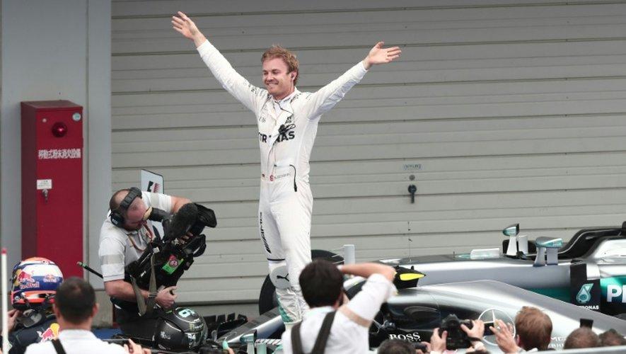 L'Allemand Nico Rosberg bras levés dans les stands après sa victoire au GP du Japon sur le circuit de Suzuka, le 9 octobre 2016