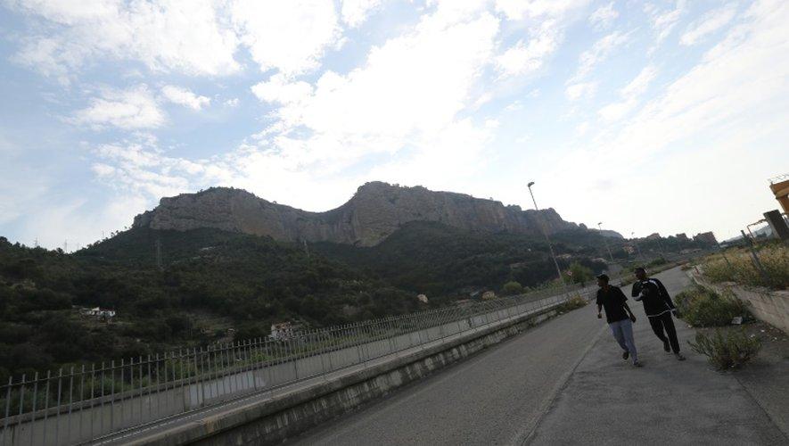 Des migrants marchent le long d'une route près de la frontière entre la France et l'Italie, le 14 septembre 2016
