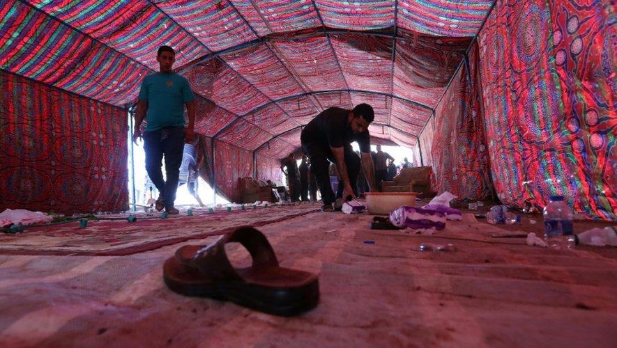 Des Irakiens nettoient le lieu d'un attentat suicide dans un quartier chiite à Bagdad, le 15 octobre 2016