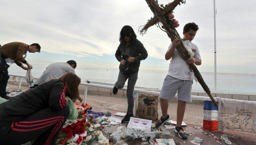 Des bénévoles ramassent les messages et objets laissés sur la Promenade des Anglais, le 16 octobre 2016, trois mois après l'attentat de Nice