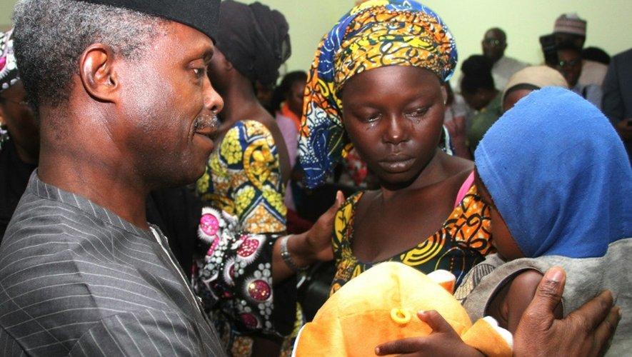 Une des 21 lycéennes de Chibok libérée pleure en tenant son bébé sous le regard du vice-président nigérian Yemi Osinbajo à Abuja le 13 octobre 2016