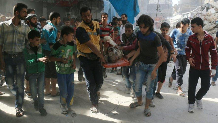 Des Syriens transportent le corps d'un homme tué après des bombardements aériens sur le quartier Fardous, dans le nord d'Alep, le 12 octobre 2016