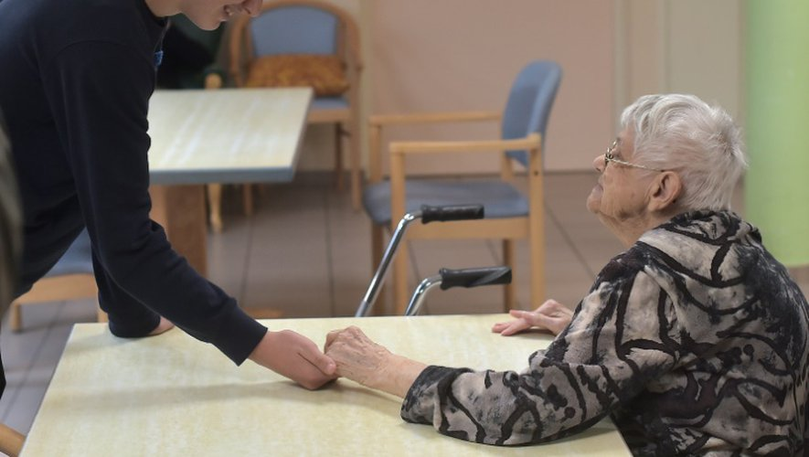 Un adolescent tient la main d'une patiente atteinte de la maladie d'Alzheimer le 18 octobre 2016 à Saint-Quirin dans l'est