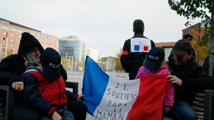 """Des enfants de policiers tiennent une banderole soutenant leurs parents """"je soutiens papa et maman"""" lors d'une manifestation de policiers, le 22 octobre à Evry"""