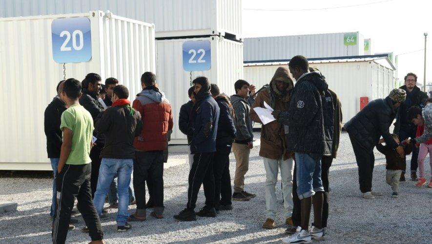 """Des migrants lisent des """"flyers"""" qui les informent du prochain démantèlement de la Jungle à Calais, le 23 octobre 2016"""