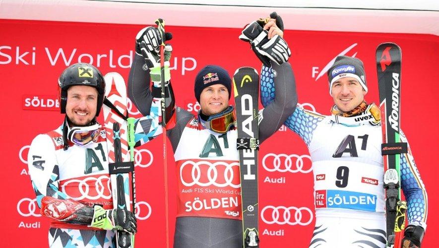 Alexis Pinturault (c) exulte sur le podium après avoir remporté le slalom géant de Sölden (Autriche), le 23 octobre 2016