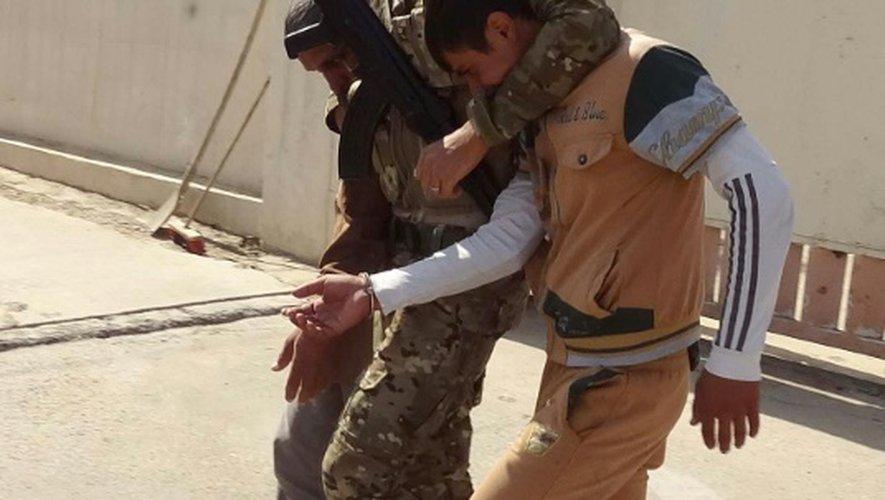 Un membre des forces de sécurité kurdes escorte un homme suspecté d'être un jihadiste de  l'EI, lors d'une patrouille à Kirkouk, le 22 octobre 2016