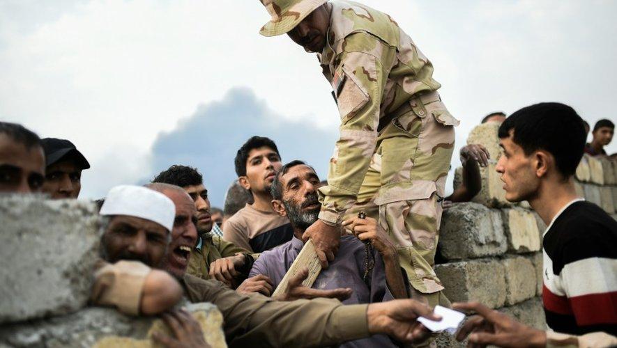Un soldat des forces armées irakiennes tente de contenir des familles de déplacés qui attendent de la nourriture, le 24 octobre 2016 à Al-Qayyarah