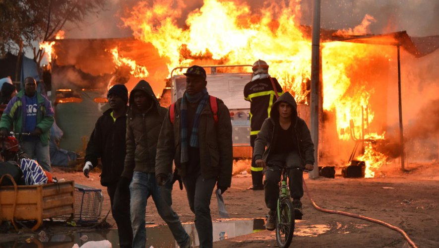 """De jeunes migrants quittent la """"Jungle"""" de Calais où un pompier tente d'éteindre un feu, le 26 octobre 2016"""