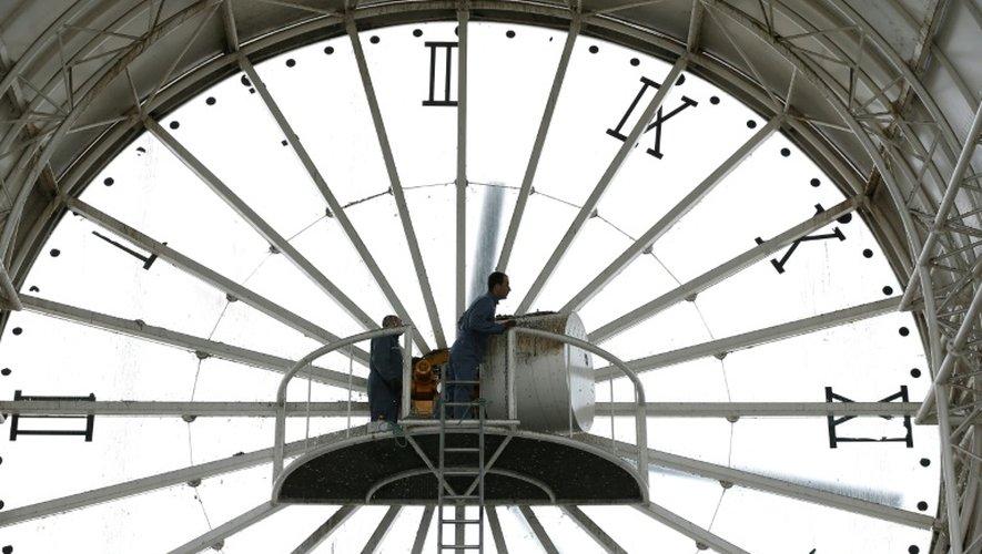Des employés entretiennent une immense horloge à Cergy dans le Val-d'Oise, le 26 mars 2015