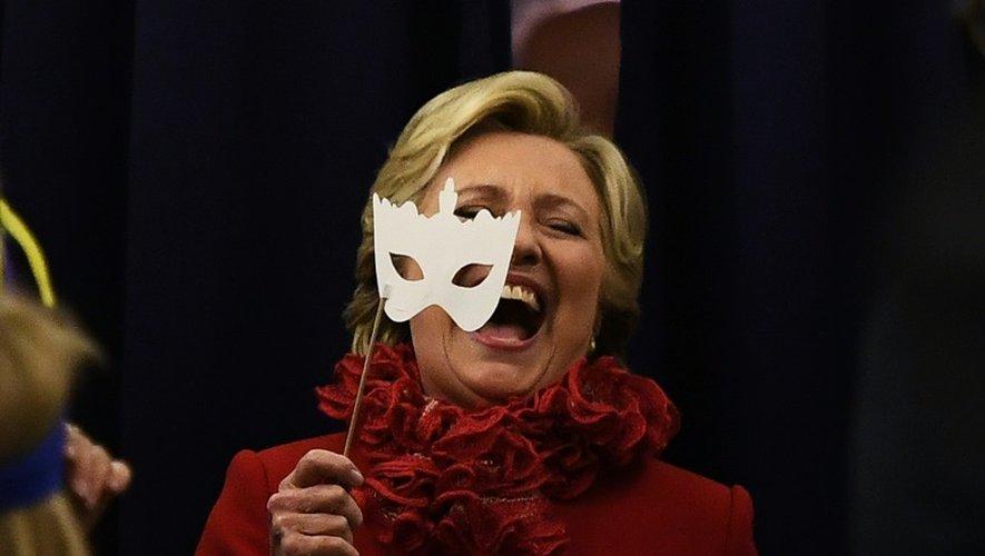 La candidate démocrate à la Maison Blanche Hillary Clinton sourit en portant un masque à bord de son avion pour la campagne électorale, le 31 octobre 2016 à Erlanger, Kentucky