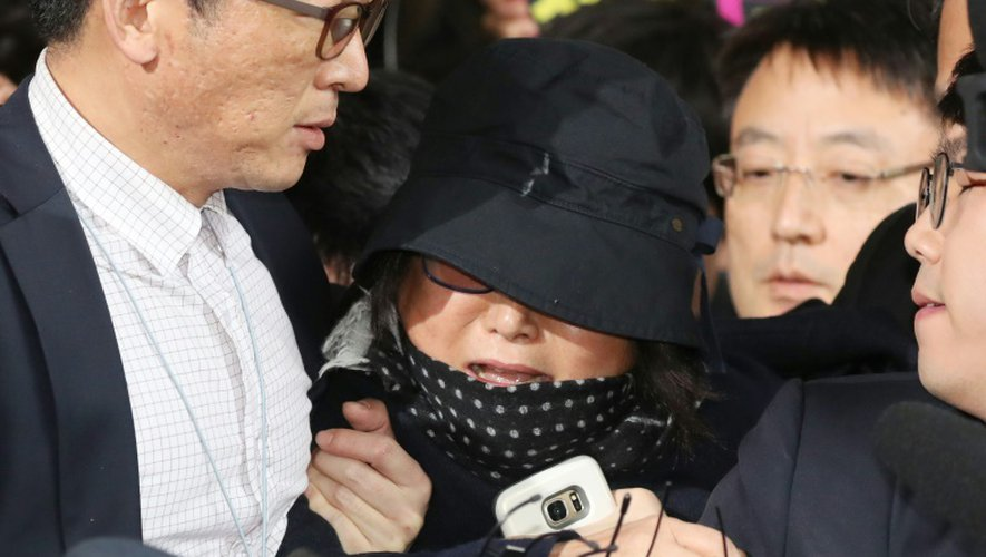 Choi Soon-Sil (c) tente de se frayer un passage, lors de son arrivée au tribunal à Séoul, le 31 octobre 2016