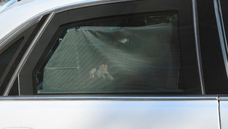 Mehdi Nemmouche caché par un rideau à bord d'une voiture de police le 12 septembre 2014 à Brxelles