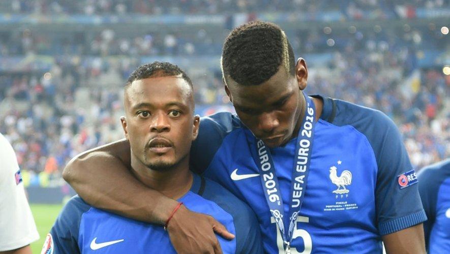 Patrice Evra (g) et Paul Pogba (d) quittent la pelouse du Stade de France dépités après la défaite des Bleus face au Portugal en finale de l'Euro-2016