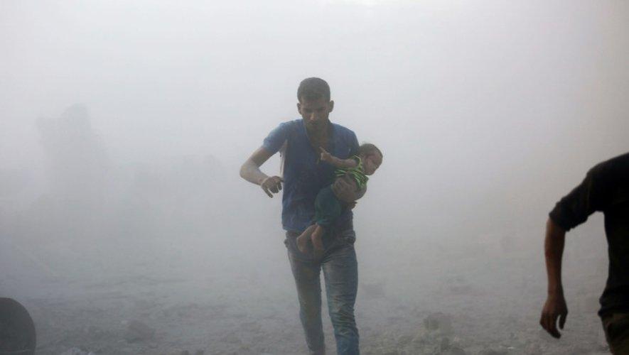 Un Syrien portant un enfant apparaît dans un nuage de poussière crée par des bombardements sur un quartier rebelle dans la banlieue de Damas, le 30 septembre 2016