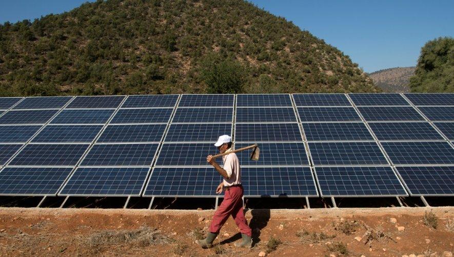 Un agriculteur marocain passe devant un panneau solaire relié à un générateur alimentant une pompe, à Tafoughalt, un petit village dans l'est du Maroc, le 31 octobre 2016