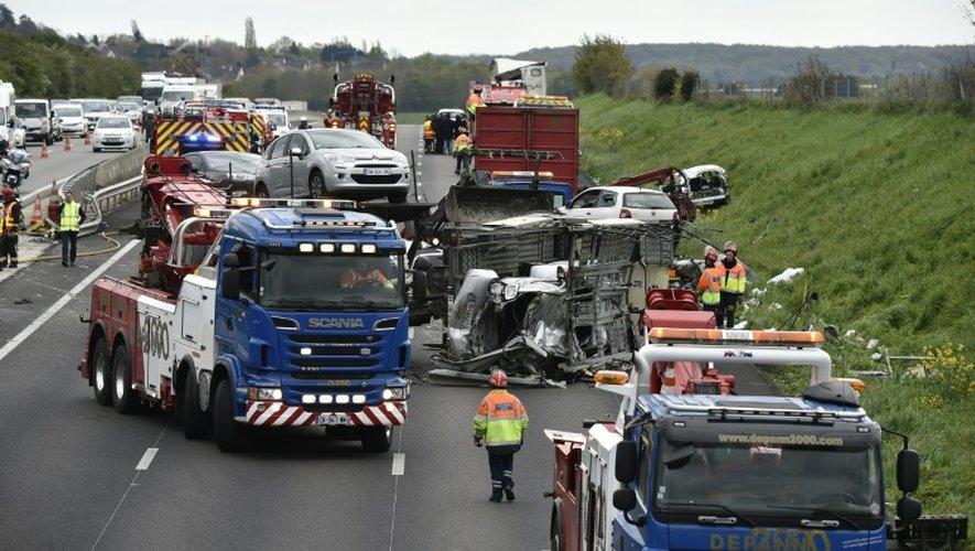 Des pompiers interviennent sur un accident entre deux camions et six voitures sur l'autoroute A13 près des Mureaux en direction de Paris, le 25 avril 2016