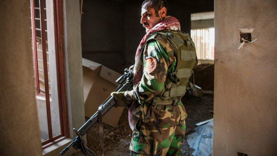 Un combattant peshmerga surveille des positions hostiles dans un immeuble de Bashiqa, le 9 novembre 2016 en Irak