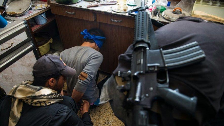Un homme suspecté d'être un combattant de l'EI arrêté par des soldats des forces d'élite irakiennes le 11 novembre 2016 à Arbagiah dans la banlieue de Mossoul