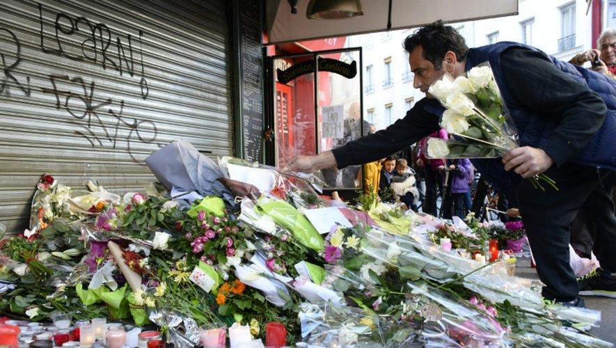 """Des fleurs en hommage aux victimes s'amoncellent le 15 novembre 2015 devant le café """"La Belle Equipe"""" à Paris"""
