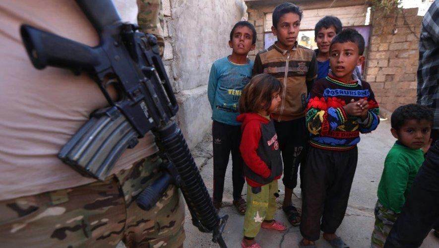 Des enfants près d'un soldat irakien patrouillant dans une rue du village de Jarif, à environ 45 kilomètres au sud de Mossoul, le 12 novembre 2016