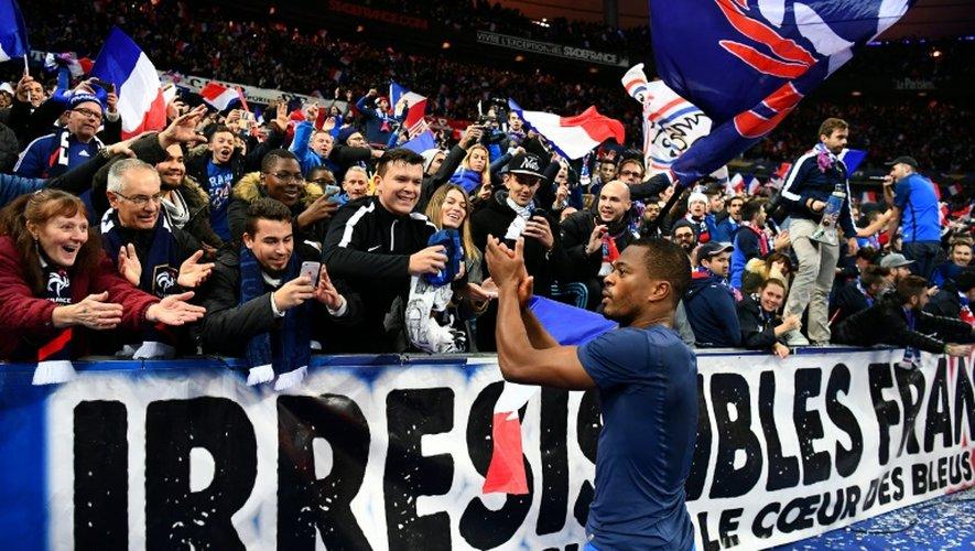 Le défenseur français Patrice Evra salue les supporters après un match contre la Suède, le 11 novembre 2016 au Stade de France