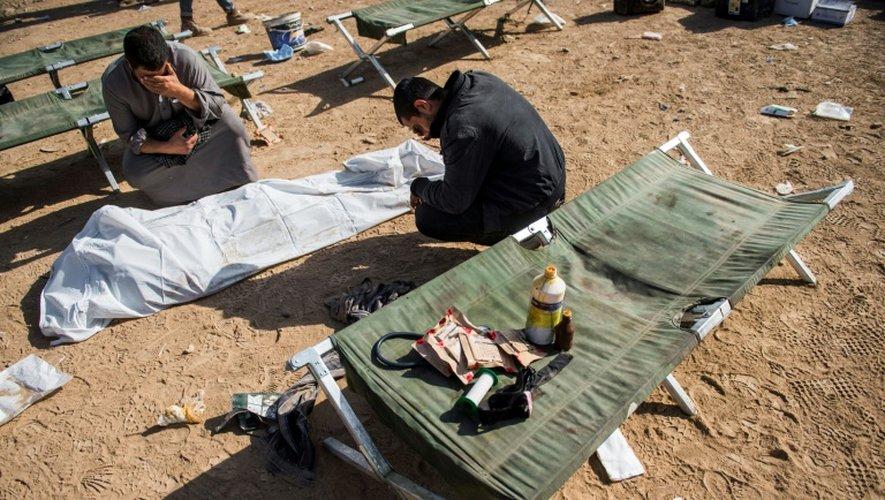Des hommes se lamentent devant le corps d'un proche dans un camp des forces spéciales irakiennes, près de Mossoul, le 17 novembre