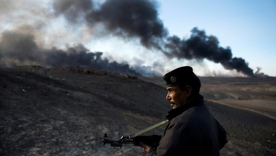 Un soldat garde le périmètre où des pomiers luttent contre le feu dans les puits de pétrole à Al Qayyarah, en Irak, le 20 novembre 2016