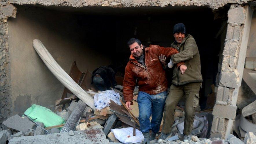 Deux syriens sortent des décombres d'un immeuble après des bombardements dans le quartier d'al-Hamra à Alep, tenu par les rebelles, le 20 novembre 2016