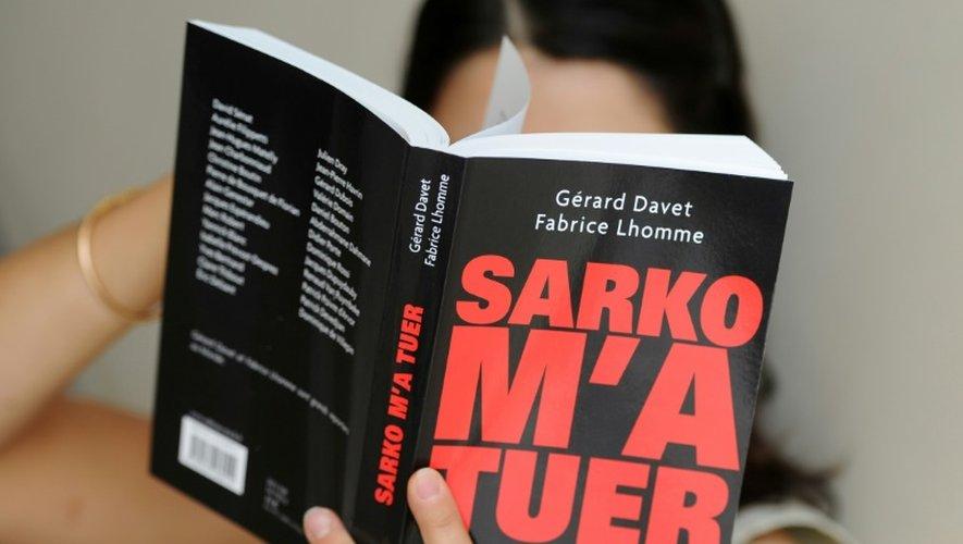 """Le livre """"Sarko m'a tuer"""" des journalistes Gérard Davet et Fabrice Lhomme entre les mains d'une lectrice le 31 août 2011 à Paris"""