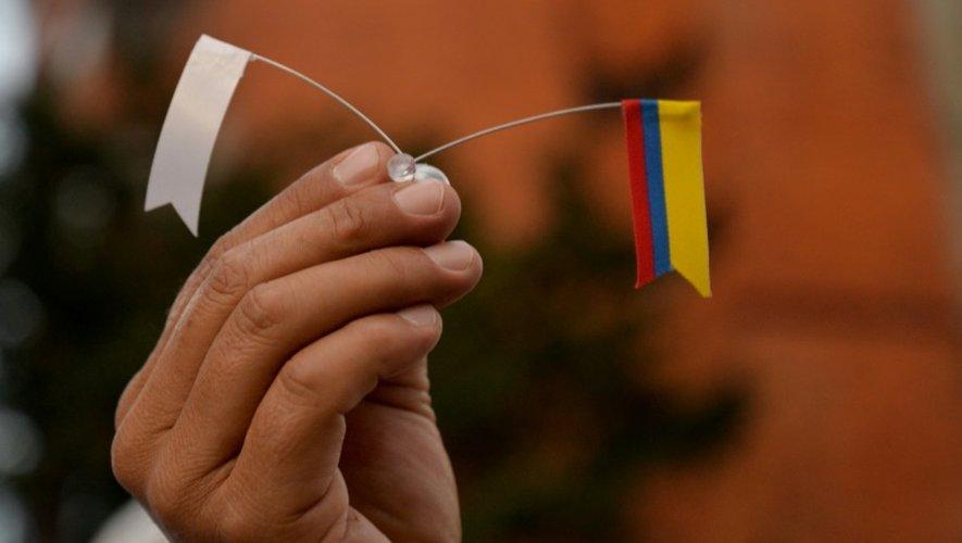 Un drapeau blanc pour la paix et un drapeau colombien tenus dans une main à Bogota par un manifestant après l'annonce d'un nouvel accord de paix, le 15 novembre.