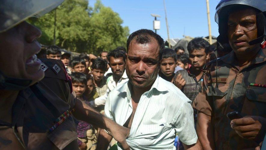 Des gardes frontières du Bangladesh arrêtent un birman (C) soupçonné par des réfugiés Rohingyas d'espionner pour la Birmanie, dans un camp de Teknaf, dans le district de Bazar de Cox, le 24 novembre 2016