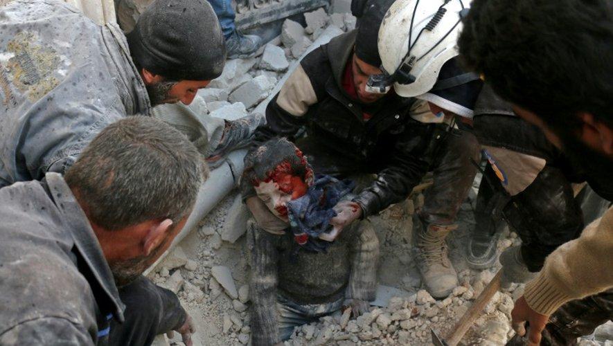 Des Casques blancs de la Défense civile syrienne sauvent un enfant des décombres d'un bâtiment détruit par un bombardement, à Bab al-Nairab, dans le nord d'Alep, le 24 novembre 2016