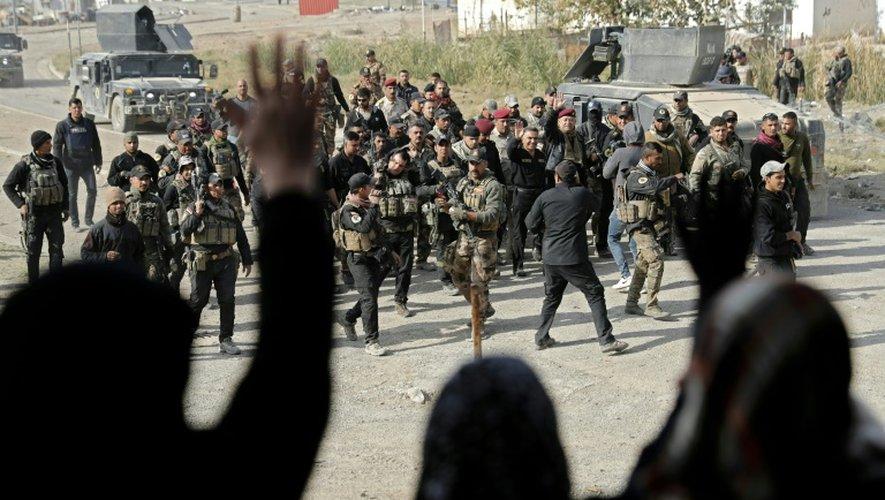 Des membres des forces spéciales irakiennes accueillis par la population dans un quartier de Mossoul repris aux jihadistes, le 27 novembre 2016 en Irak