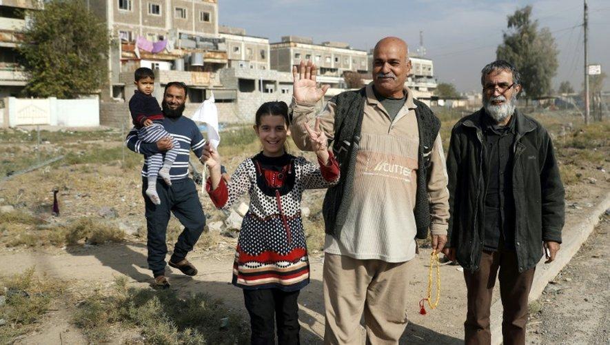 Des habitants dans une rue d'un quartier de Mossoul récemment repris aux jihadistes salue les forces irakiennes, le 27 novembre 2016 en Irak